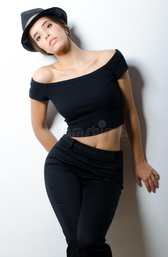 Beautiful fashionable girl in black clothes leaning against white wall.  royalty free stock images