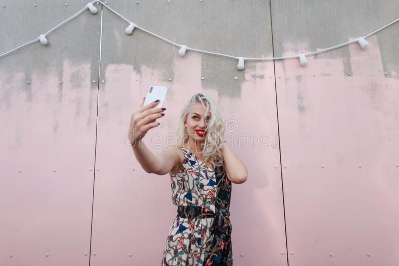 Beautiful fashionable girl in a fashionable dress makes selfie. On the phone near the pink wall at a party stock image