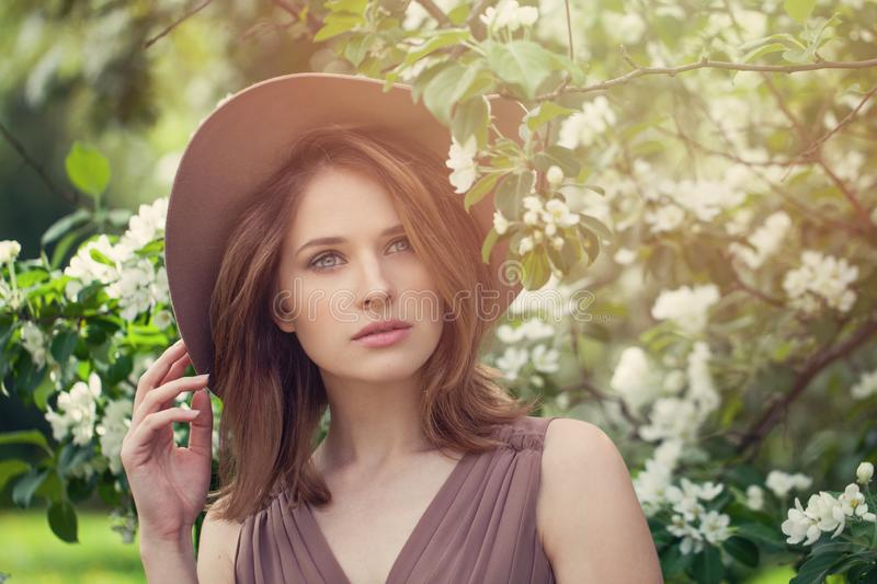 Beautiful fashionable girl in fedora hat in spring flowers garden stock photography