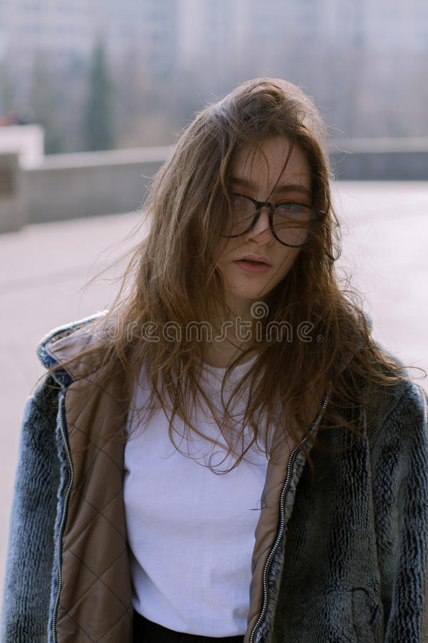 A beautiful and fashionable girl in a fur coat walks in the city on a sunny day. A stylish girl in glasses and a fur coat walks on a sunny day in an urban city stock photo