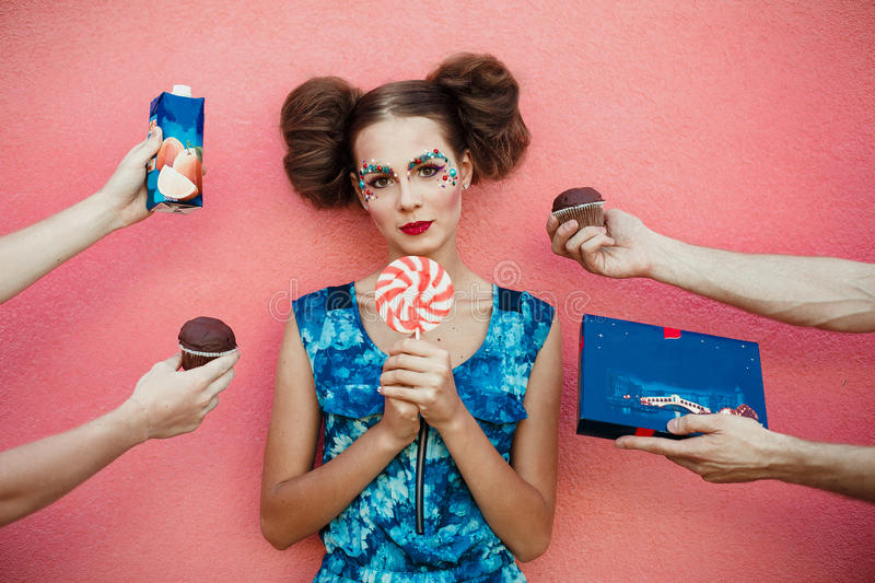 Beautiful fashionable girl with two hair bun a creative makeup holding a huge pink sweet lollipop in hands. Many hands on pink bac stock images