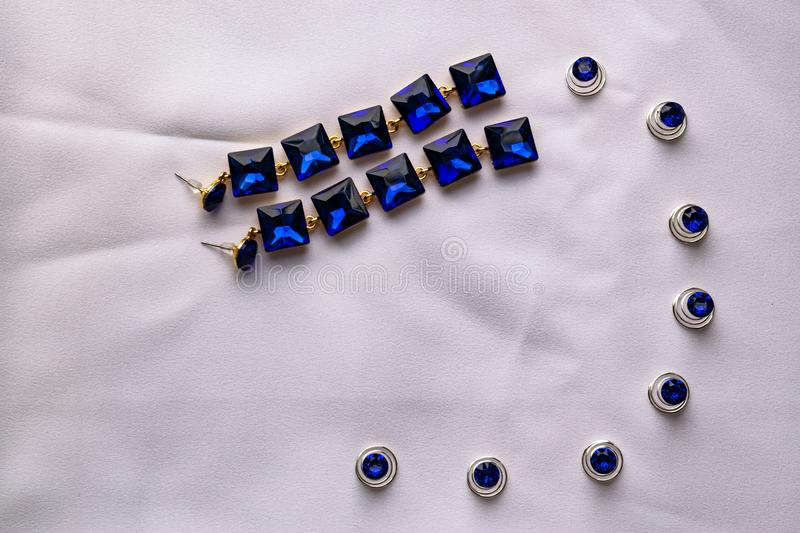 Beautiful and fashionable jewelry and accessories for women. Sapphire earrings with square stones on white textile background. Blu royalty free stock image