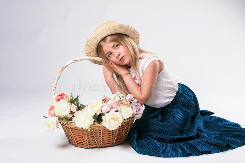 Beautiful fashionable little girl with blond hair with a basket of flowers and a straw hat kanotier royalty free stock photo