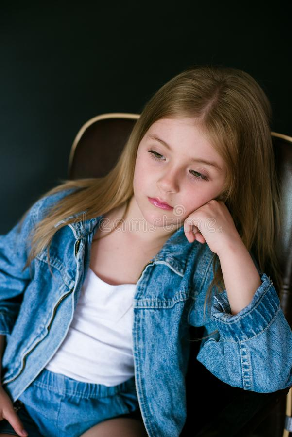 Beautiful fashionable little girl with blond hair in jeans clothes on a black background stock photo