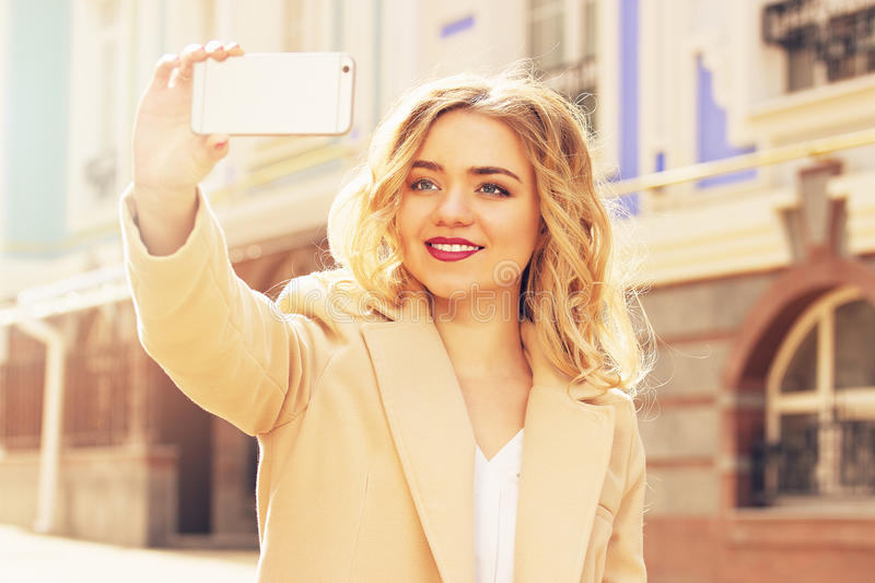 Beautiful and fashionable smiling blond hair girl taking selfie on her phone. Womens fashion. Beautiful girl walking the city. Womens fashion stock photos