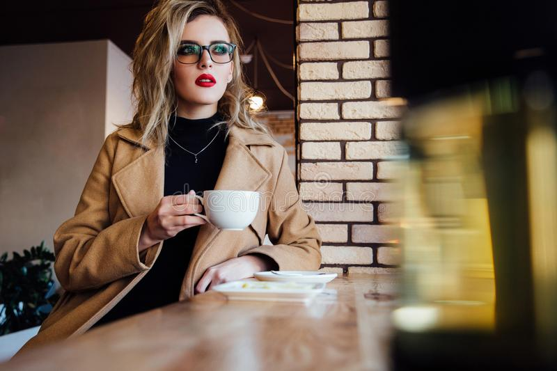 Beautiful fashionable stylish girl sits in a cafe with a cup of coffee. royalty free stock photos