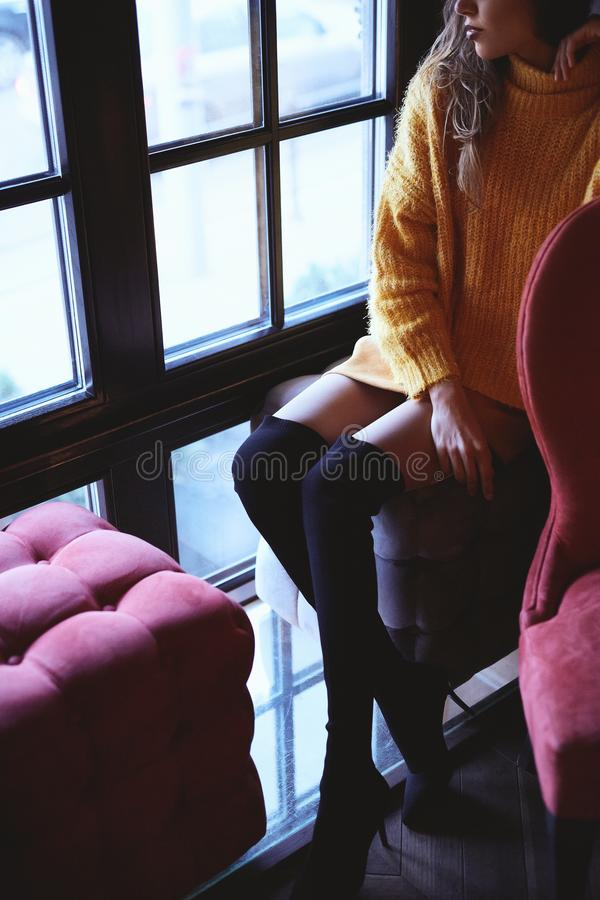 Beautiful fashionable woman in bright yellow sweater and skirt and knee high heel boots walking and posing indoors stock photography