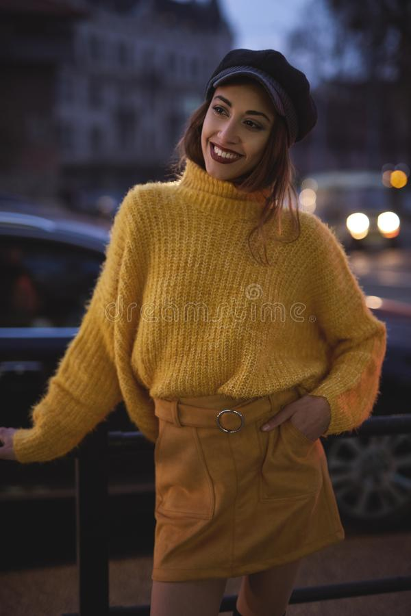 Beautiful fashionable woman in bright yellow sweater and skirt and knee high heel boots walking and posing outdoors stock image