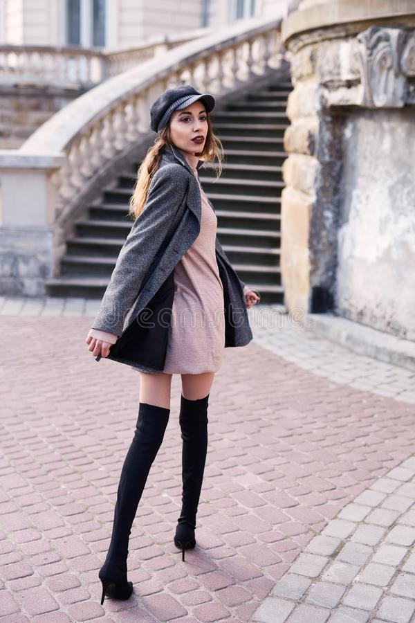 Beautiful fashionable woman in gray coat and black knee high heel boots walking and posing outdoors stock photos
