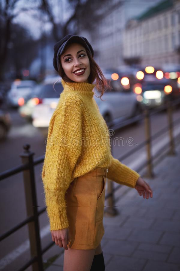 Beautiful fashionable woman in bright yellow sweater and skirt and knee high heel boots walking and posing outdoors royalty free stock photo