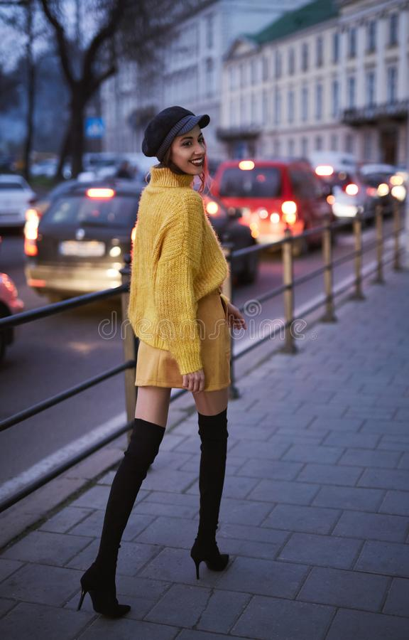 Beautiful fashionable woman in bright yellow sweater and skirt and knee high heel boots walking and posing outdoors stock images