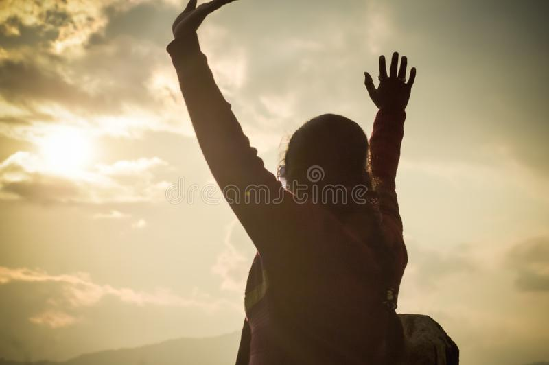 Beautiful fashionable woman enjoying holiday in sunset sun of orange sky background, raise hands up in air close up, back view royalty free stock photos