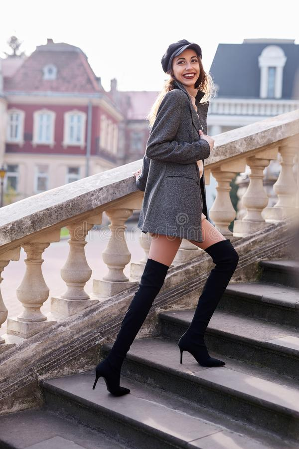 Beautiful fashionable woman in gray coat and black knee high heel boots walking and posing outdoors royalty free stock photo