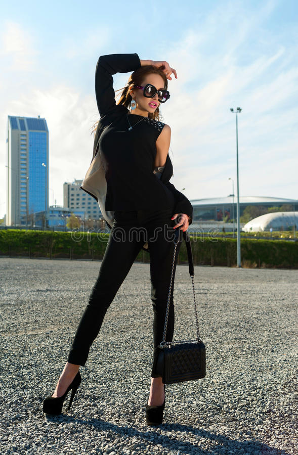 Beautiful fashionable woman in the street. On a sunny day royalty free stock image