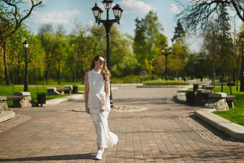 Beautiful and fashionable young blonde woman in white dress posing outdoors in park royalty free stock image