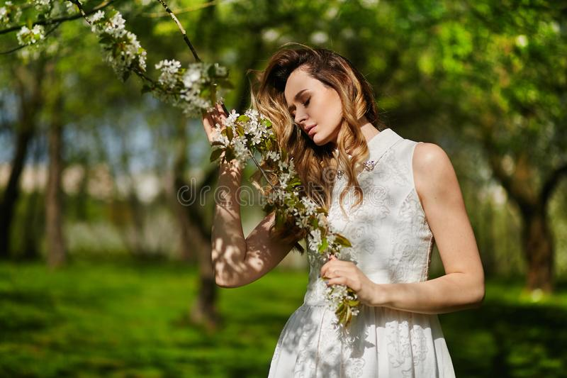 Beautiful and fashionable young blonde woman in white dress posing outdoors in park royalty free stock photos