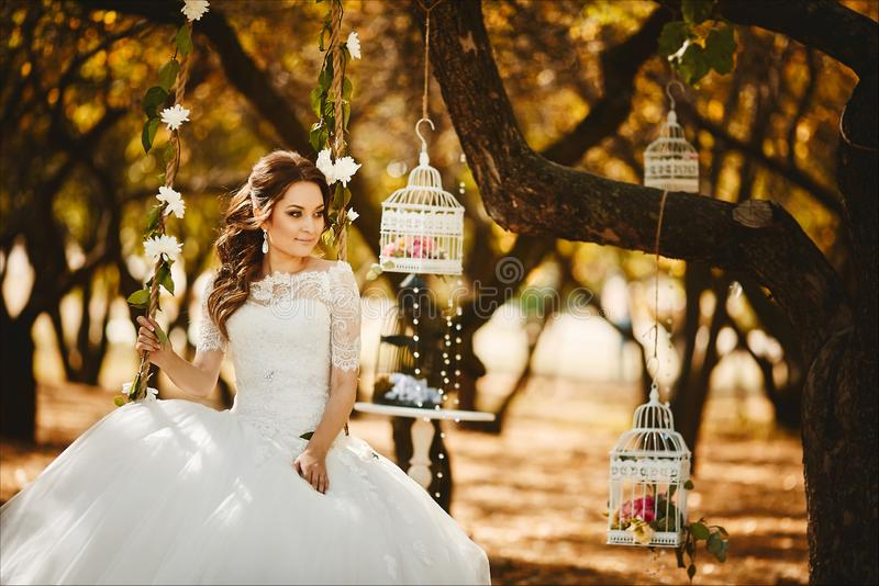 Beautiful and fashionable young bride with trendy hairstyle in stylish wedding lace dress sits on the hanging swings stock photos