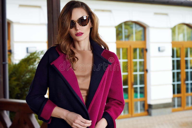 Beautiful fashionable young business woman wearing in ?rimson autumn coat and sunglasses with hairdo and makeup walking on a royalty free stock photo