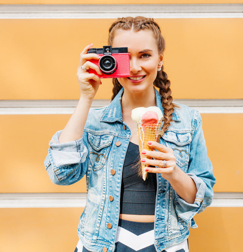 Beautiful fashionable young girl posing in a summer dress and denim jacket with pink vintage camera and multi-colored ice cream. stock photos
