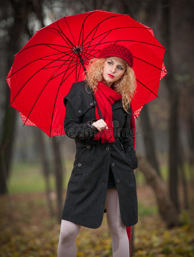 Beautiful Fashionable Young Girl With Red Umbrella , Red Cap And Red Scarf In The Park Royalty Free Stock Photo