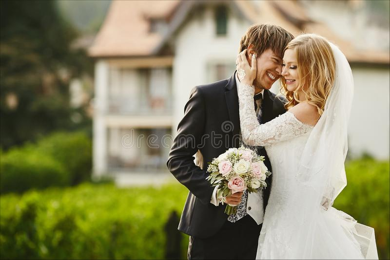 A beautiful and fashionable young model woman in the wedding dress hugs with the stylish handsome young man in a stock image
