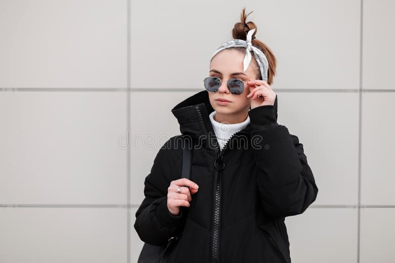 Beautiful fashionable young woman hipster with a stylish hairstyle in black glasses in a stylish black coat with a bandana. With a black backpack on her royalty free stock photos