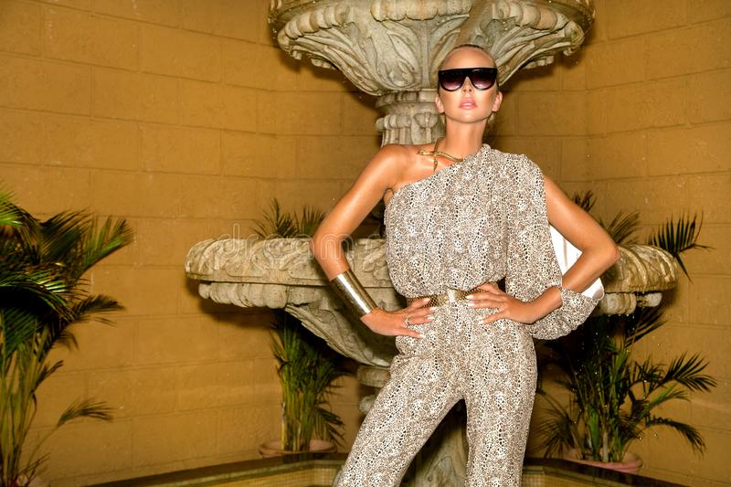 Beautiful fashionable young woman posing in the park, sunglasses, jumpsuit, high heels, blonde hair. Fashion summer photo. Bright royalty free stock photography