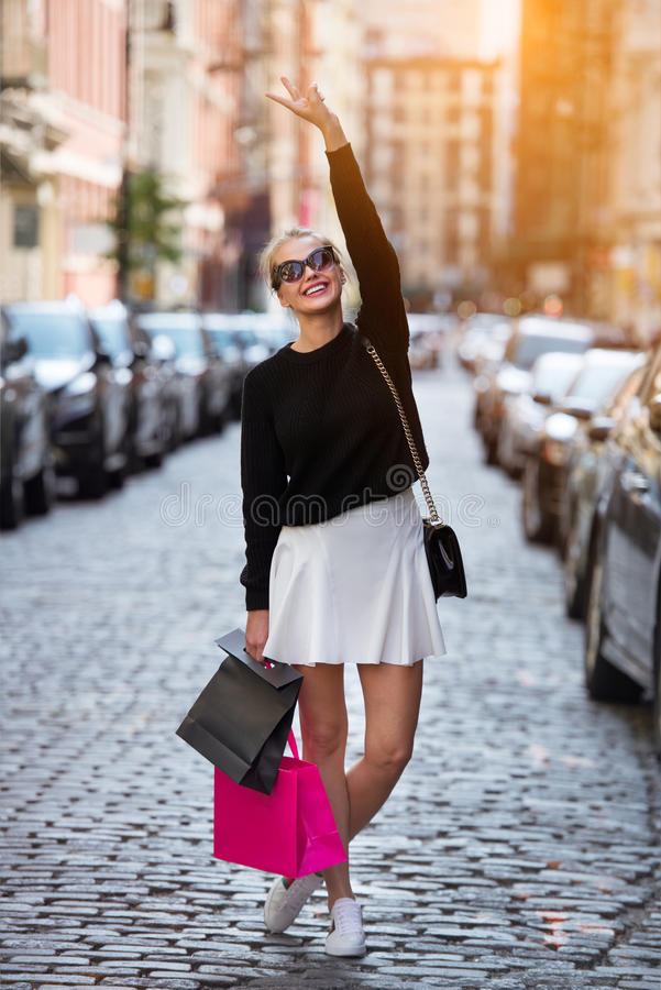 Beautiful fashionable young woman with shopping bags walking on city street and having fun. stock images