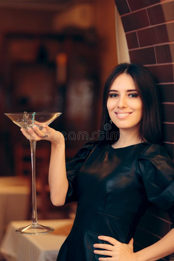 Woman Holding Giant Champagne  Glass Filled with Jewelry royalty free stock image