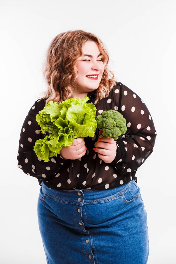 Beautiful fat young woman with bright emotions on a light gray background. Concept of diet. Space for text. stock photos