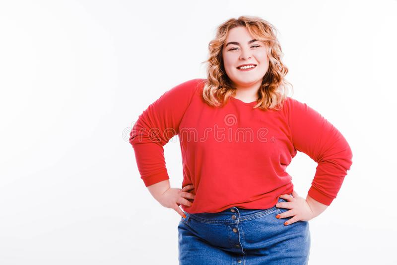 Beautiful fat young woman with bright emotions on a light gray background. Concept of diet. Space for text. royalty free stock photos