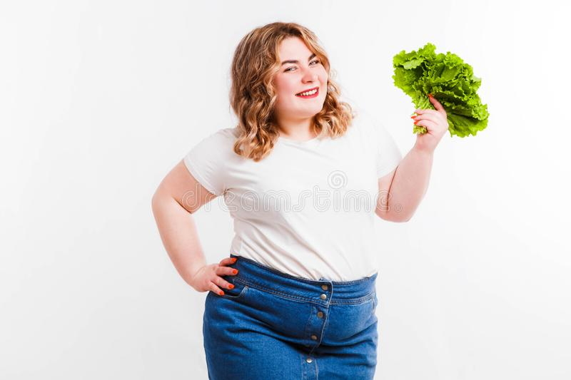 Beautiful fat young woman with bright emotions on a light gray background. Concept of diet. Space for text. royalty free stock photography