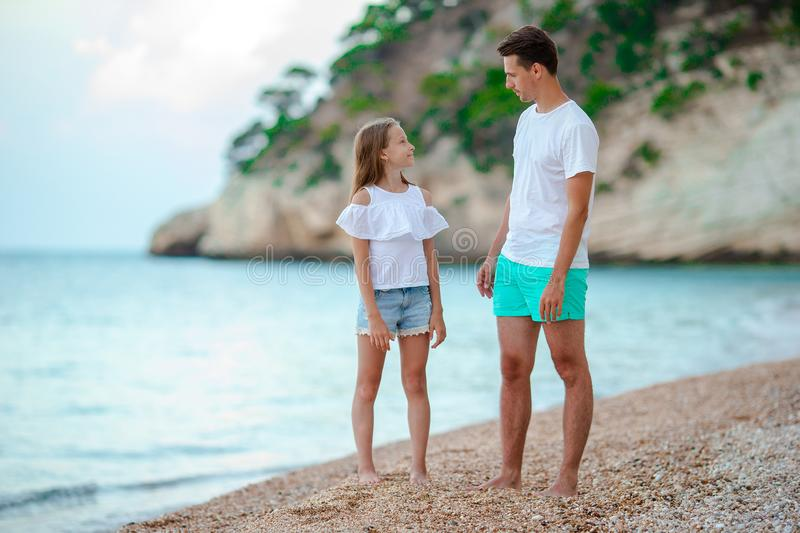 Beautiful father and daughter on european beach. Young father and his adorable little daughter on summer vacation on pebble beach royalty free stock photography