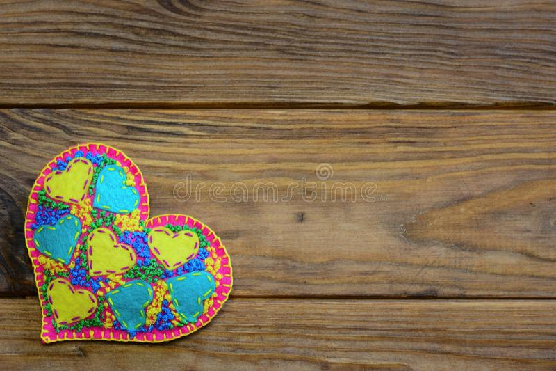 Beautiful felt heart decoration for Valentines Day. Applique heart decoration isolated on a wooden background with empty place royalty free stock image