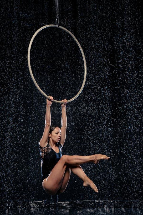 Beautiful female acrobat hanging with graceful pose on aerial hoop under rain on black background. Beautiful female acrobat hanging on aerial hoop under rain on royalty free stock photo