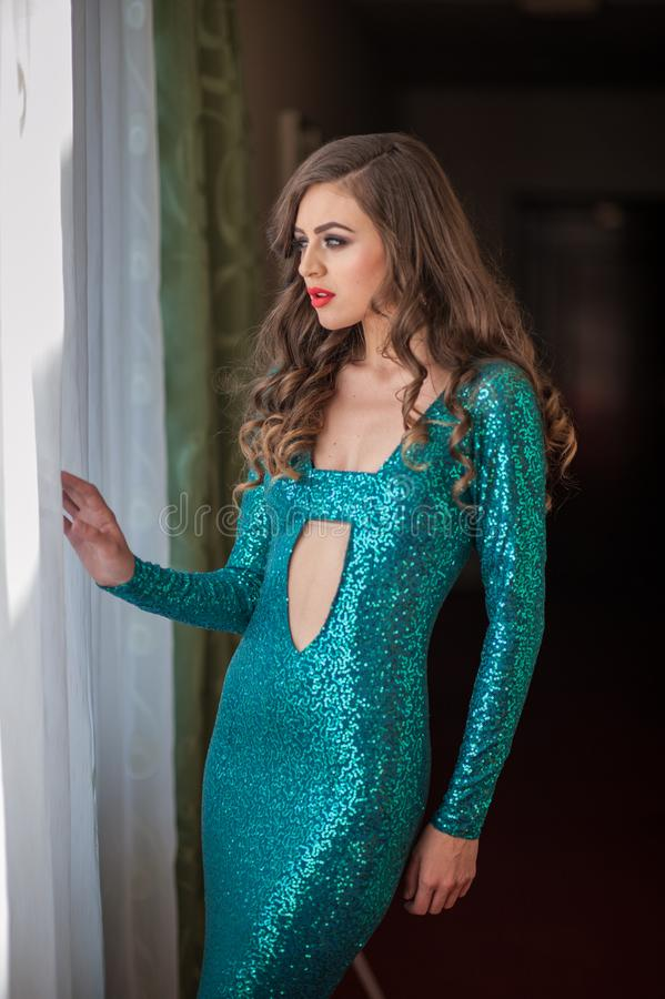 Beautiful female art portrait with beautiful eyes on the window. Elegance. Long hair brunette in long dress. Portrait of a at royalty free stock image