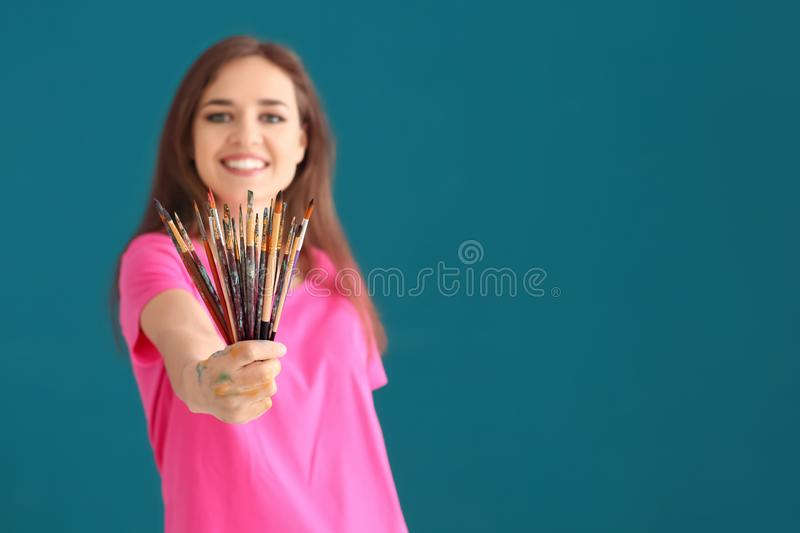 Beautiful female artist with set of brushes on color background stock photography