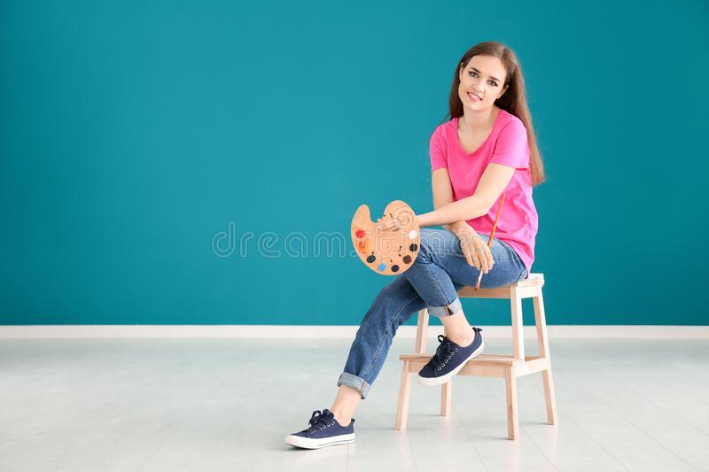 Beautiful female artist sitting on stool against color wall stock photography