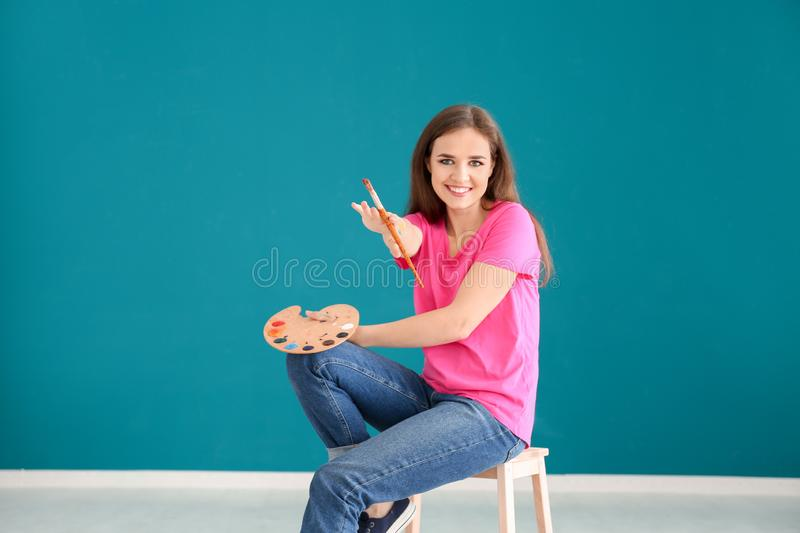 Beautiful female artist sitting on stool against color wall royalty free stock photos