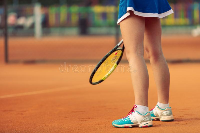 Beautiful female athlete with perfect body posing on tennis court, close up stock image