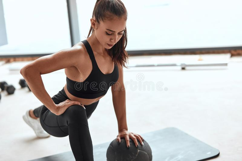 Beautiful female athlete performs push ups on fitness ball. Attractive caucasian girl in sportswear do push up with ball. White gym background stock photo