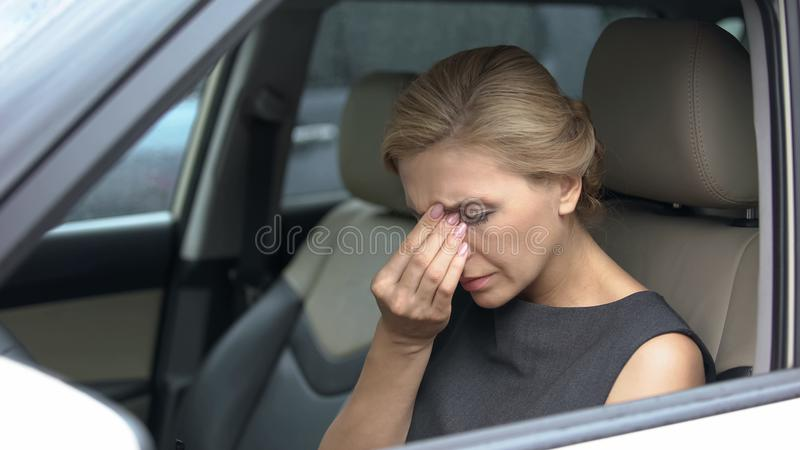 Beautiful female in automobile feeling eye pain, exhaustion after long trip. Stock photo stock image