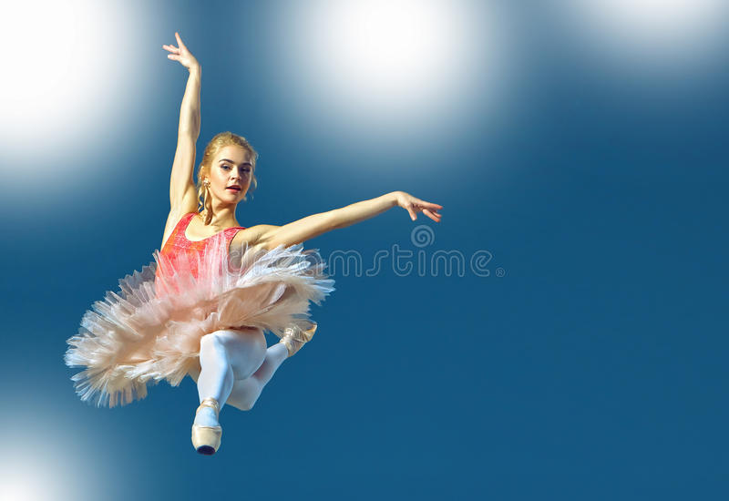 Beautiful female ballet dancer on a grey background. Ballerina is wearing pink tutu and pointe shoes. royalty free stock photos