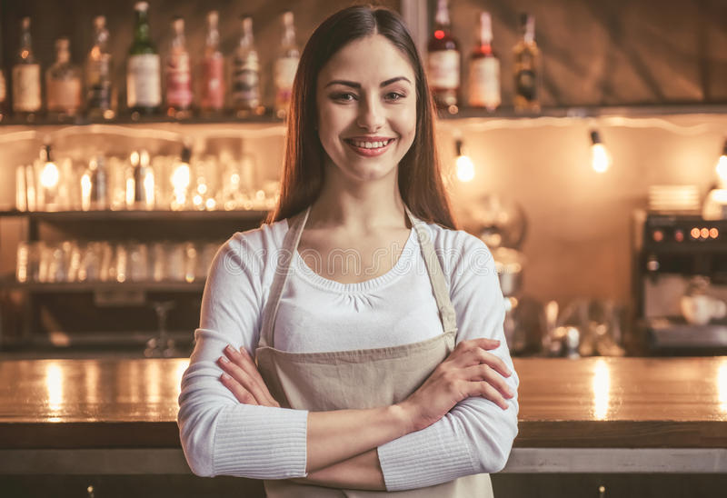 Beautiful female barista. Is looking at camera and smiling while standing with folded arms near the bar counter in cafe stock photography