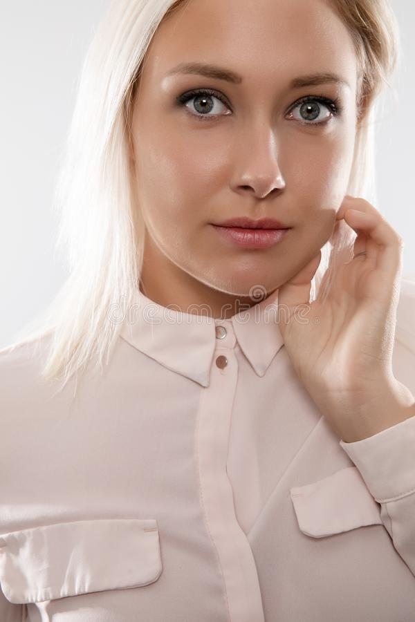 Beautiful female blonde model in shirt holding her hair royalty free stock images