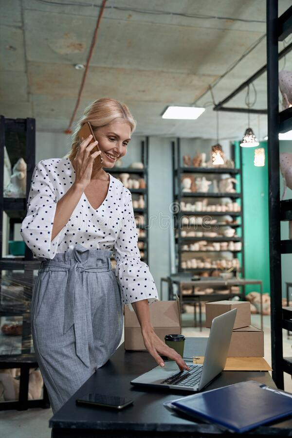Free Beautiful Female Business Owner Or Succesful Businesswoman Taking An Order By Phone And Using Laptop While Working In Royalty Free Stock Photo - 198156265