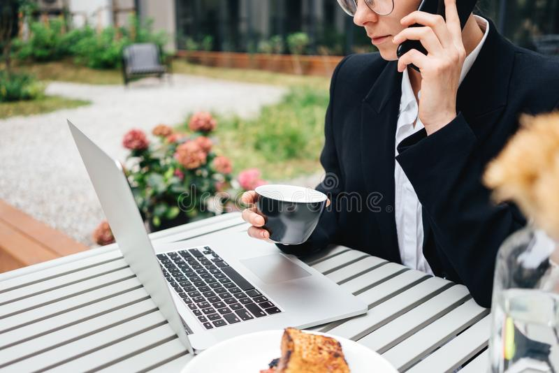 Beautiful female business talking on smartphone while sitting at coffee shop and working on laptop. Young businesswoman sitting at cafe on veranda having stock photography