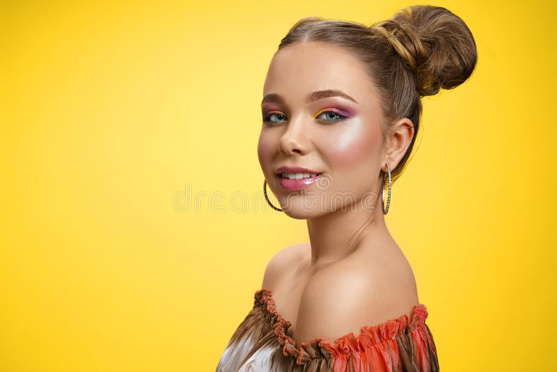 Pretty girl with colorful makeup posing on yellow background stock image