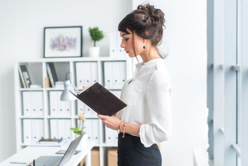 Beautiful female clerk standing in office at her workplace, holding planner, reading timetable for the day, side view royalty free stock photography
