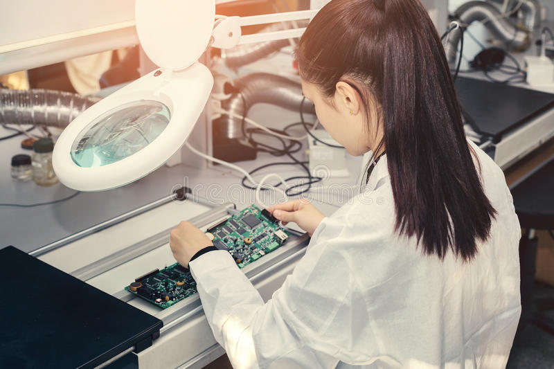 Beautiful female computer expert professional technician examining board computer in a laboratory in a factory stock images